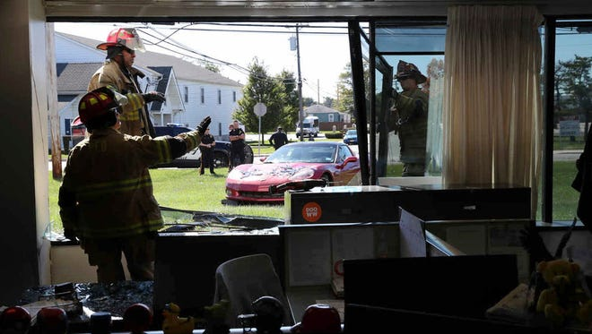 Firemen clear glass after a car drove into The Press of Atlantic City business and editorial office and crashed the window into the newsroom, in Pleasantville, N.J., Tuesday, Oct. 17, 2017.