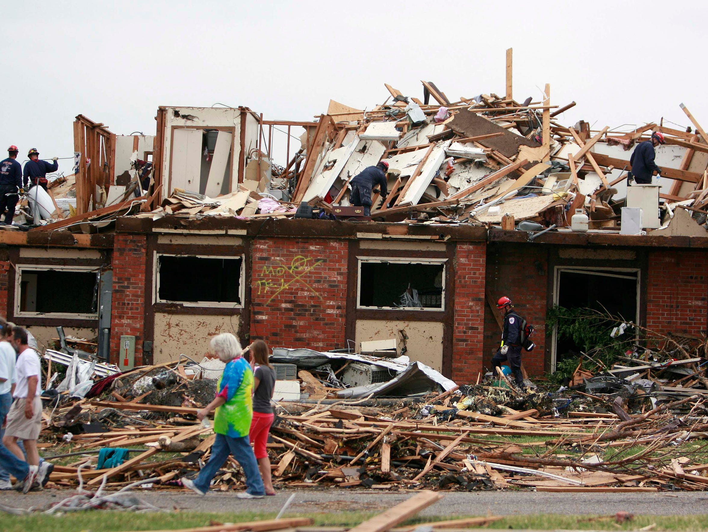 Passerby's walk past a destroyed apartment complex