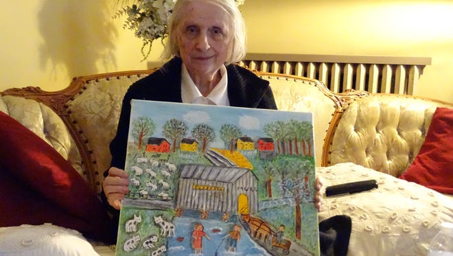 Bernadine Stetzel displays one of her paintings during an interview with The News-Messenger in July 2015. The Fremont artist passed away in August 2016 and will be honored with a retrospective at the Way Library in Perrysburg.