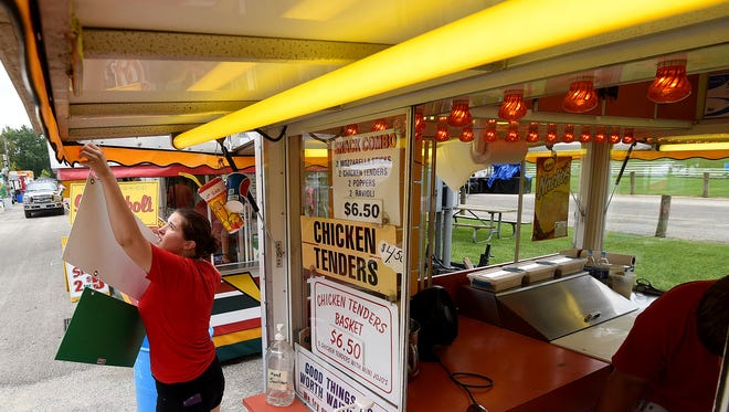 Saliece Burrows of Massillon hangs a sign outside the Ohio's Favorite Corn Dog and Fried Cheese concession in preparation for the opening of the Blueberry Festival in Lexington.