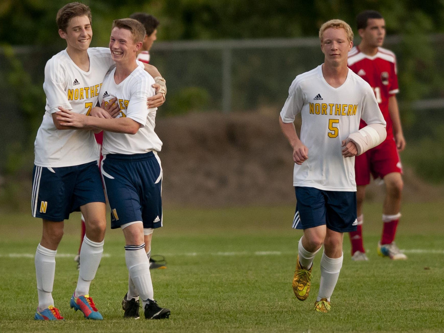 Port Huron Northern junior Jeremy Sayers, center, celebrates scoring a goal with junior James Robertson during a soccer game Thursday, September 24, 2015 at Port Huron Northern High School.