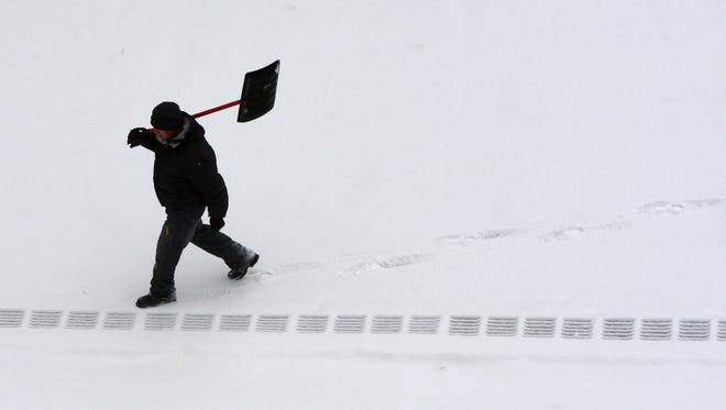 A person walks with his snow shovel along Rumsey Road in Yonkers.