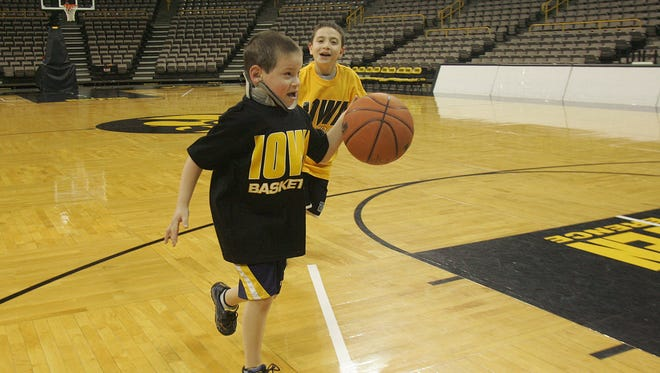 In this file photo from 2006, Jesse Weiss, then 7, plays basketball with his older brother Aaron, then 11, at Carver-Hawkeye Arena before a men's basketball team practice.
