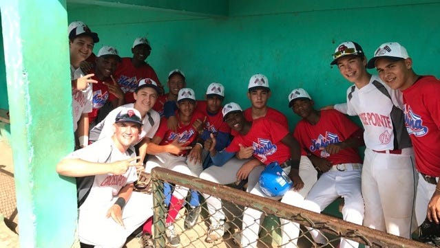 Members of the Grosse Pointe Avengers, a Michigan-based youth travel baseball team, pose with Cuban players during their trip to the island country.