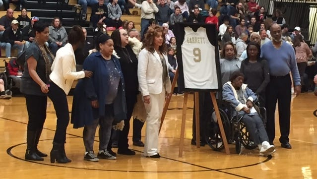 Bill Garrett's family poses with his retired No. 9 at Shelbyville High School on Wednesday night.