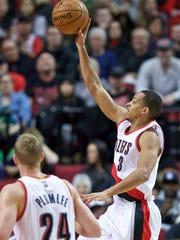 Portland Trail Blazers guard C.J. McCollum, right, shoots the ball against the Orlando Magic during the first half of an NBA basketball game in Portland, Ore., Saturday, March 12, 2016.