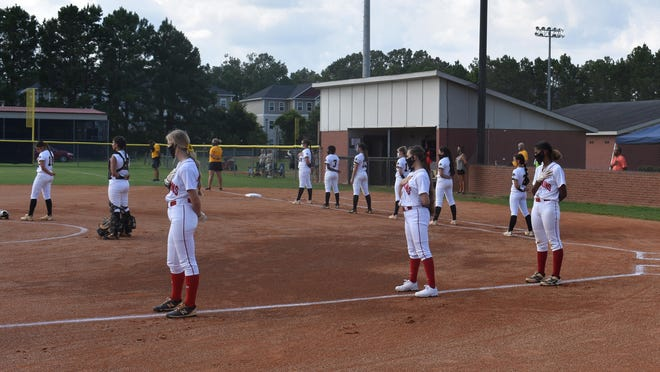 Players practice social distancing during the national anthem before the Bryan County and Richmond Hill softball teams played Aug. 12 at Richmond Hill.