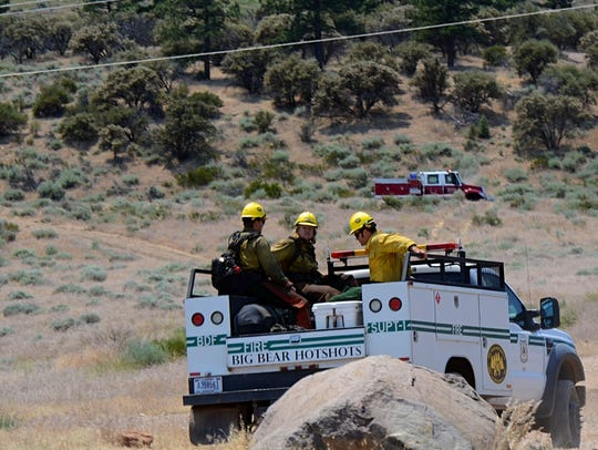 A crew of firefighters are seen at the back of a vehicle