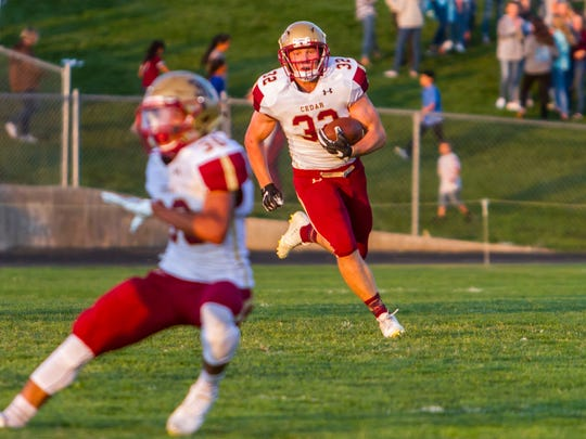 Cedar running back Trenton Maurer (32) carries the