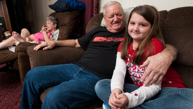 Monroe Mulder sits with his granddaughter Mady at his home in Wetumpka, Ala., on Tuesday December 15, 2015. in the background is Mulder's disabled wife Ann.