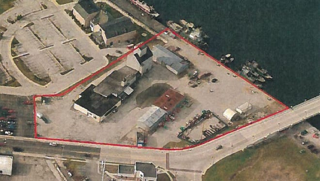 An aerial photograph taken in 2011 shows the Sturgeon Bay West Waterfront area (outlined in red) before the former Door County Cooperative buildings were razed. Friends of the Sturgeon Bay Public Waterfront argue that the land next to the still-standing old grain elevator is within Lake Michigan's ordinary high-water mark and therefore can't be resold to a private developer.