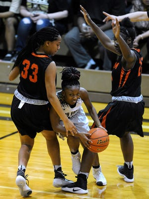 Abilene High's Sandrine Tuyizere (2) passes the ball to a teammate while being guarded by a pair of Haltom defenders during the fourth quarter of the Lady Eagles' 51-46 loss on Tuesday, Feb. 7, 2017, at Abilene High School.