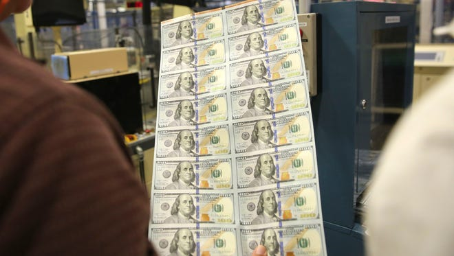 A sheet of uncut $100 bills is inspected during the printing process at the Bureau of Engraving and Printing Western Currency Facility in Fort Worth, Texas on Sept. 24, 2013. Annual pay raises are becoming increasingly rare at companies.