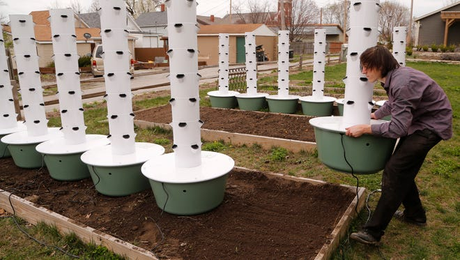 Austin Kasso sets up garden towers Monday, April 3, 2017, in a lot near Wabash Avenue and Ellsworth streets in Lafayette. Kasso will grow a variety of vegetables in 12 garden towers. He plans to give 30 percent of what he grows away for free. The remaining 70 percent will be sold through City Foods and in local farmers markets.