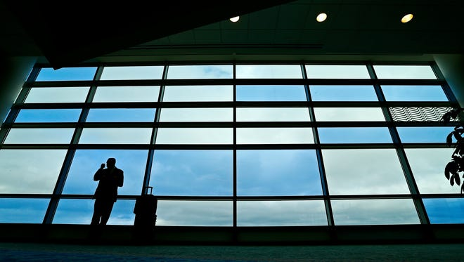 Dan Pfaff, a captain for NetJets Inc., stands in front of a window at the Springfield-Branson National Airport in Springfield, Mo. as he waits to board his flight to Charlotte, N.C. on Nov. 4, 2015.