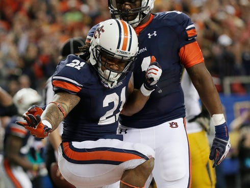 Auburn running back Tre Mason (21) strikes a Heisman pose as he celebrates a touchdown against Missouri during the second half of the Southeastern Conference championship NCAA college football game in Atlanta. Mason is one of six finalist for the Hei