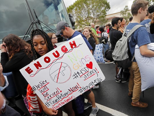 Tyra Hemans, 19, who survived the shooting at Stoneman Douglas High School, waits to board a bus in Parkland, Fla., Feb. 20, 2018.   The students plan to hold a rally Wednesday in hopes that it will put pressure on the state's Republican-controlled Legislature to consider a sweeping package of gun-control laws, something some GOP lawmakers said Monday they would consider.