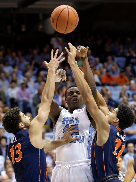 North Carolina's Joel James hoots as Virginia's Anthony Gill (13) and Isaiah Wilkins (21) defend during the first half of an NCAA college basketball game in Chapel Hill, N.C., Monday, Feb. 2, 2015. (AP Photo/Gerry Broome)