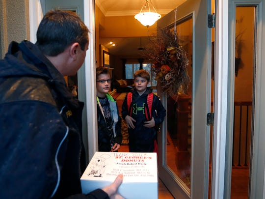 Jaxson Nibert (center), a 2nd grader at Wilder Elementary, and his brother Cooper greet Fire Capt. Jeff Prior at their front door and gave him donuts on Tuesday, Nov.17, 2015. Jaxson was the winner of a drawing the fire department held to win ride to school in a fire truck.