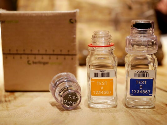 FILE - In this Dec. 12, 2016, file photo, the A and B sample bottles from the latest Berlinger Special BEREG-Kit for human urine doping testing stand posed for photographs in London. The Swiss manufacturer of the bottles used around the world to hold doping control samples says it is pulling out of the niche industry. Berlinger's withdrawal from the market poses a major headache for anti-doping agencies, who are now scrambling to find alternative suppliers. (AP Photo/Matt Dunham, File)