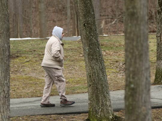 Dressed for the cool, overcast weather, a man walks Sunday at Van Saun County Park in Paramus.