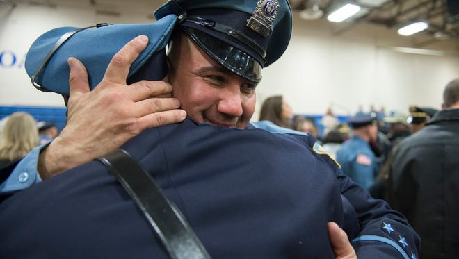 Vineland police officer Felipe Laboy, right hugs his nephew, newly graduated Vineland police officer Bobby B. Laboy as the Gloucester County Police Academy holds its 51st graduation ceremony Wednesday, Dec. 13, 2017 in Sewell, New Jersey.