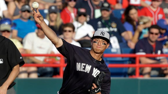 New York Yankees third baseman Rob Refsnyder throws out a Washington Nationals runner in the third inning of a spring training baseball game, Wednesday, March 23, 2016, in Viera, Fla.