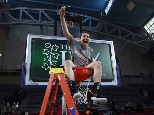 Princeton's Gabrielle Rush raises her piece of net as she sits in the basket following an NCAA college basketball championship game against Pennsylvania in the Ivy League Tournament, Sunday, March 11, 2018, in Philadelphia. (AP Photo/Chris Szagola)