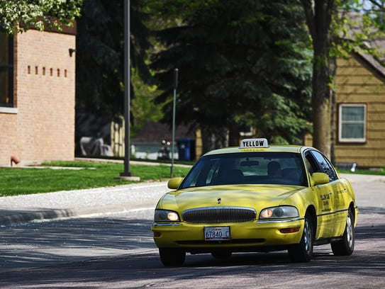 A Yellow Cab taxi pulls up to Horace Mann Elementary