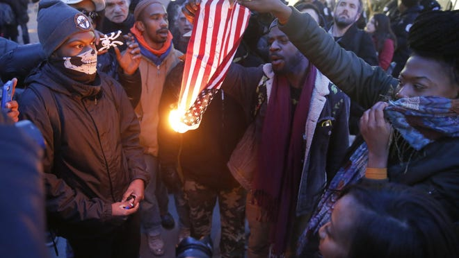 """FILE - In this Feb. 23, 2016 file photo, protesters burn an American flag in Chicago. Champaign County Ill., State's Attorney Julia Rietz was alerted on July 4, 2016, that police had just arrested a resident on suspicion of burning an American flag. Rietz said she knew """"immediately"""" that the Urbana Police Department needed to release him. The state law used to jail him, though clear in its prohibition of desecrating either the U.S. or state flags, is unconstitutional. (AP Photo/Charles Rex Arbogast, File)"""