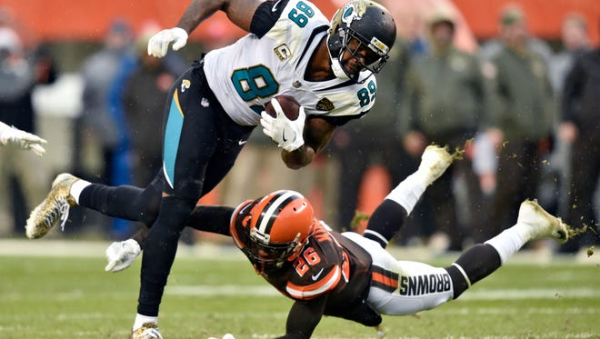 Jacksonville Jaguars tight end Marcedes Lewis (89) is tackled by Cleveland Browns strong safety Derrick Kindred (26) in the first half of an NFL football game, Sunday, Nov. 19, 2017, in Cleveland.