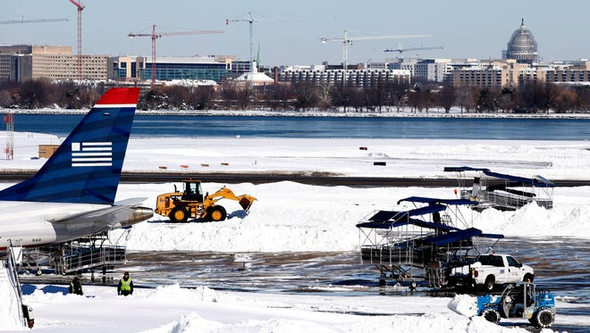 Workers clear snow on the tarmac at  Ronald Reagan National Airport, with the U.S. Capitol dome in the background, Jan. 24, 2016 in Arlington, Va.
