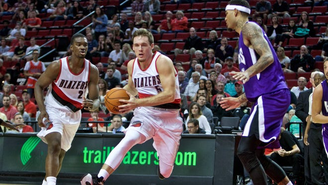Portland Trail Blazers guard Pat Connaughton, center, drives to the basket past Sacramento Kings center Willie Cauley-Stein during the second half of an NBA preseason basketball game in Portland, Ore., Monday, Oct. 5, 2015.