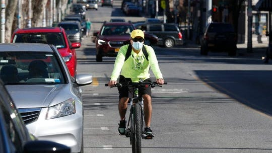 A cyclist travels along Main Street in Beacon while wearing a surgical mask on March 27, 2020.