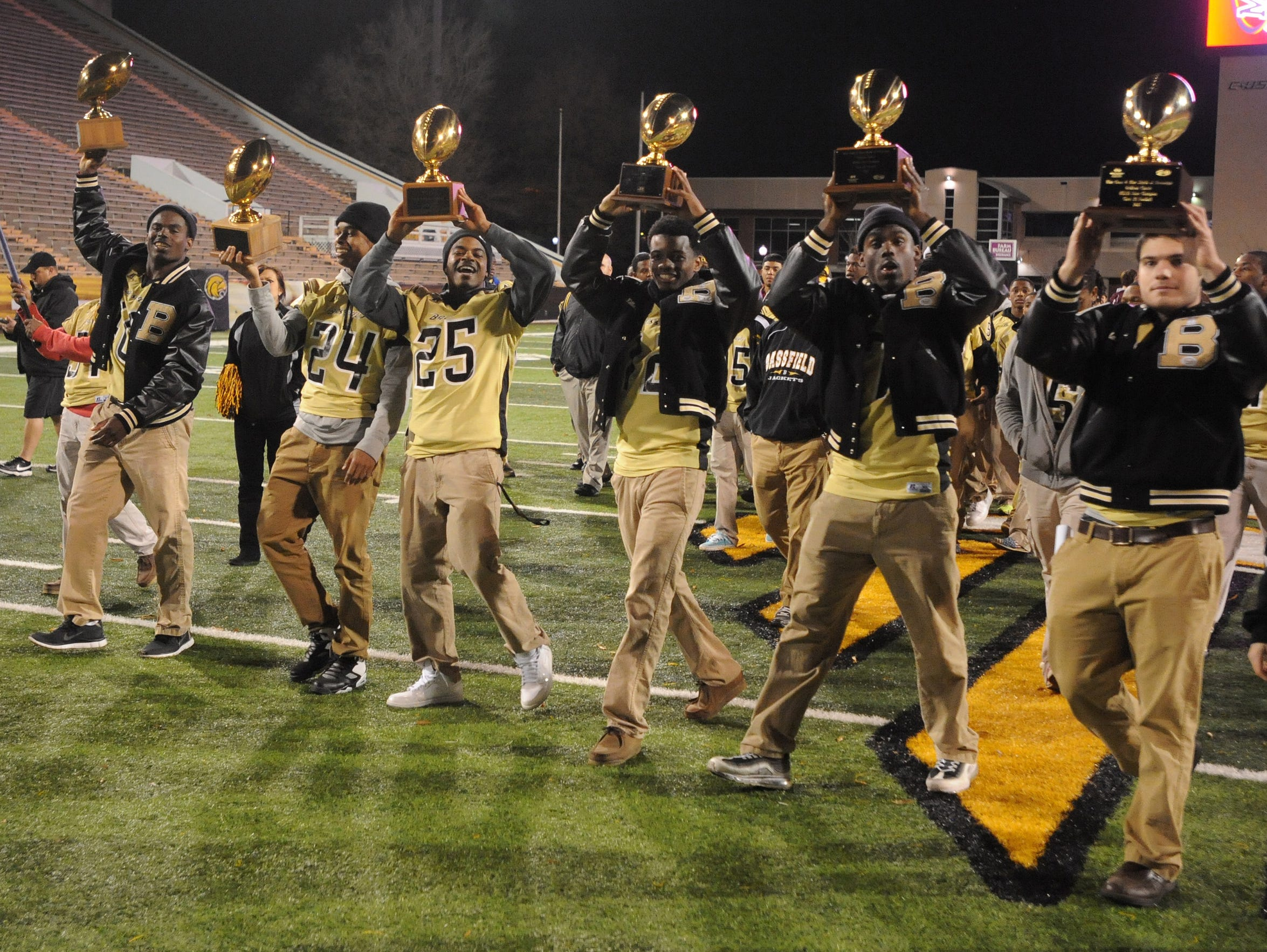 A group of former Bassfield High star football players hoists the program's state championship trophies during a ceremony in 2013 at M.M. Roberts Stadium.