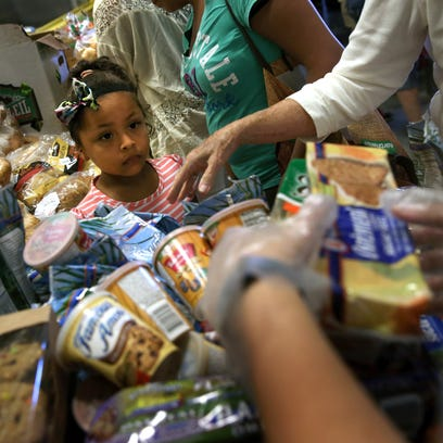 Low-income residents select free bread and produce at the Community Food Bank of New Jersey on August 28, 2015 in Egg Harbor, New Jersey.