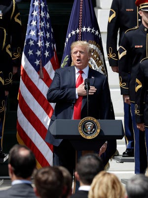 "President Donald Trump sings the national anthem during a ""Celebration of America"" event on the South Lawn of the White House, Tuesday, June 5, 2018, in Washington. Trump quickly scheduled the event with military bands after canceling a visit with the Philadelphia Eagles as he stoked fresh controversy over players who protest racial injustice by taking a knee during the national anthem. (AP Photo/Evan Vucci) ORG XMIT: DCEV201"