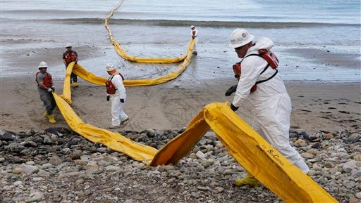 Workers prepare an oil containment boom at Refugio State Beach, north of Goleta, Calif., Thursday, May 21, 2015. More than 7,700 gallons of oil has been raked, skimmed and vacuumed from a spill that stretched across about 9 miles of California coast, just a fraction of the sticky, stinking goo that escaped from a broken pipeline, officials said. (AP Photo/Jae C. Hong)