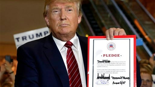 Republican presidential candidate Donald Trump holds his pledge during a news conference, at Trump Tower in New York,  Thursday, Sept. 3, 2015. Trump ruled out the prospect of a third-party White House bid and vowed to support the Republican Party's nominee, whoever it may be.