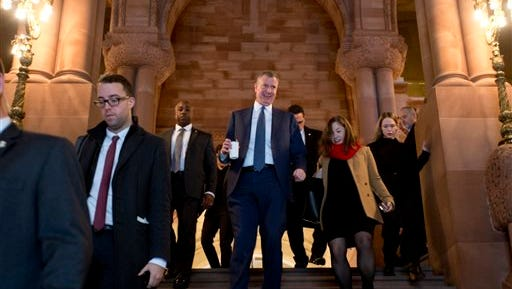 New York City Mayor Bill de Blasio, center, walks down the Great Western Staircase at the Capitol on Wednesday, Jan. 13, 2016, in Albany, N.Y.