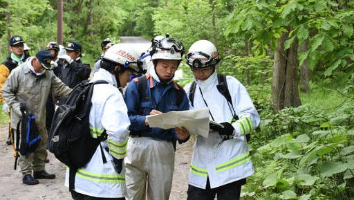 Rescuers search for a 7-year-old boy who is missing in a Japanese forest in Nanae town, on Hokkaido, the northernmost of Japan's four main islands Monday, May 30, 2016.