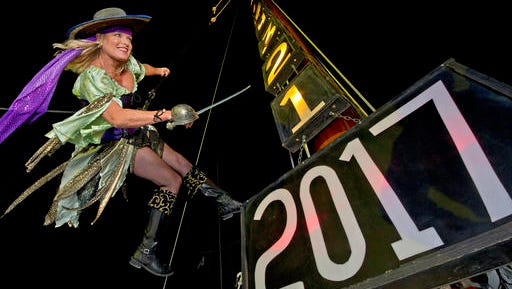 In this Friday, Dec. 30, 2016, photo provided by the Florida Keys News Bureau, Evalena Worthington, costumed as a pirate wench, practices being lowered from the mast of the sailing vessel America 2.0 outside the Schooner Wharf Bar in Key West, Fla. Emotionally wrenching politics, foreign conflicts and shootings at home took a toll on Americans in 2016, but they are entering 2017 on an optimistic note, according to a new poll that found that a majority believes things are going to get better for the country next year.