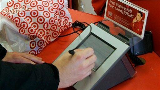 A customer signs his credit card receipt at a Target store in Tallahassee, Fla. Target says that about 40 million credit and debit card accounts customers may have been affected by a data breach that occurred at its U.S. stores between Nov. 27, 2013, and Dec. 15, 2013. (AP Photo/Phil Coale, File)