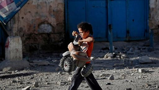 A Palestinian girl walks with a toy that she salvaged from debris of the el-Yazje apartment building which was destroyed following an overnight Israeli missile strike in Gaza City Thursday.