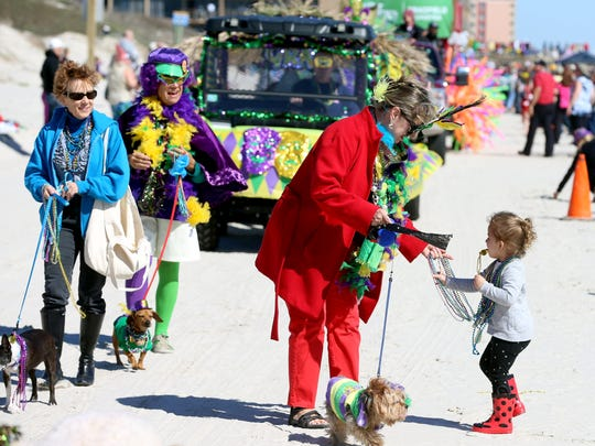 Members of Padre Island Dog Park hand beads and candy to spectators during the seventh annual Barefoot Mardi Gras parade Saturday, Feb. 6, 2016, in Corpus Christi.
