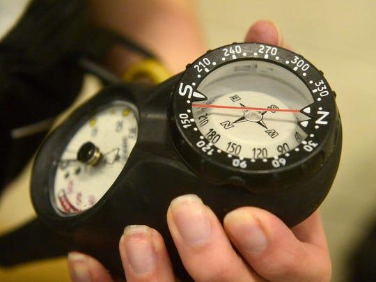 Scuba diving console holds a diver's compass, depth