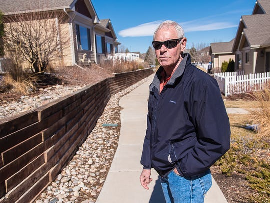 Mike Pretz, homeowner and resident of Liberty at Registry Ridge, stands in front of a failing retaining wall in his subdivision, on Wednesday, March 1, 2017.
