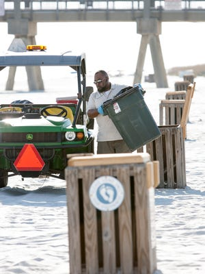 Escambia County Public Works maintenance worker Christopher Dwayne Horne empties trash cans along Casino Beach in Pensacola on Thursday, September 29, 2016.