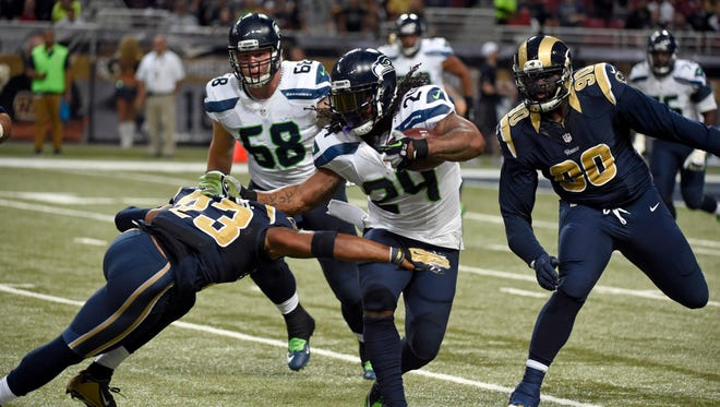 Seattle Seahawks running back Marshawn Lynch (24) runs with the ball as St. Louis Rams free safety Rodney McLeod (23) and defensive tackle Michael Brockers (90) defend and Seahawks' offensive tackle Justin Britt watches during the second quarter of an NFL football game Sunday, Sept. 13, 2015, in St. Louis.