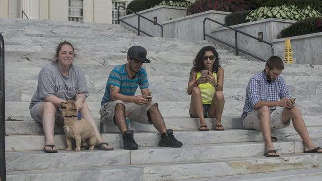 People gather on the steps of the State Capitol in downtown Montgomery to play Pokemon Go on Thursday, July 14, 2016.
